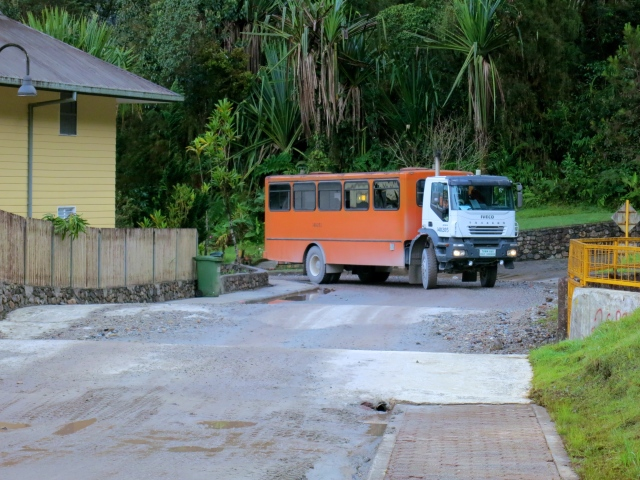 An MZIS school bus coming around the corner to pick-up the students at the bus stop.