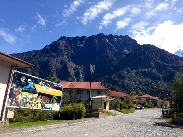 "This is a picture of our neighborhood, Hidden Valley.  The beautiful Mt. Zaagkam stands commandingly above this apartment lined street.  Company posters, which add a bit of  industrial whimsy to neighborhood, are common around all parts of town.  Loosely translated, the sign means, ""Lets work safely and with spirit."""