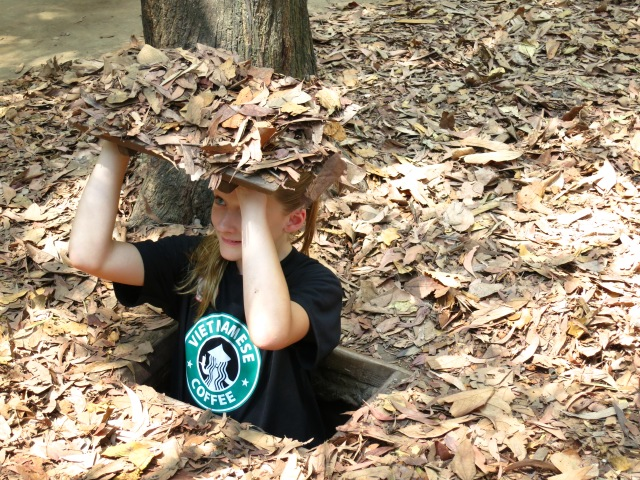 This is a picture of Ally standing in a camouflaged  trap door at the Cu Chi Tunnels.