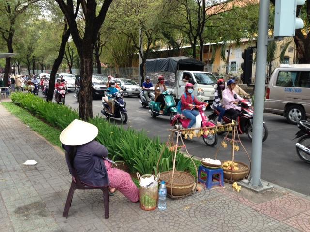 A street vendor taking a nap in the hot Saigon sun.