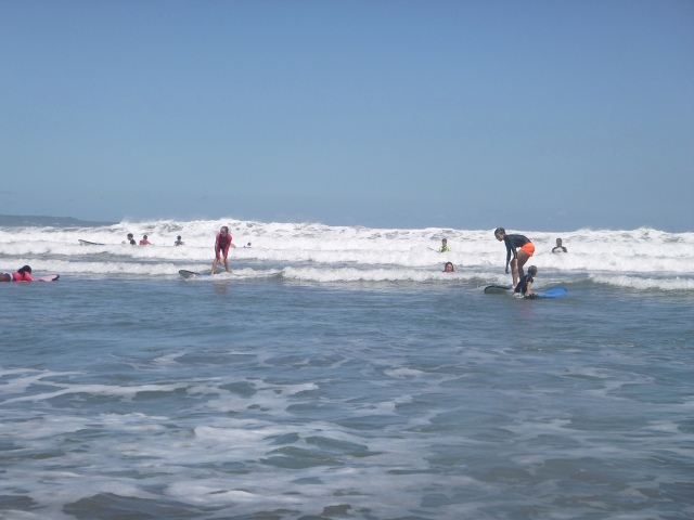 Ally and her friend, Summer, catching a small wave.