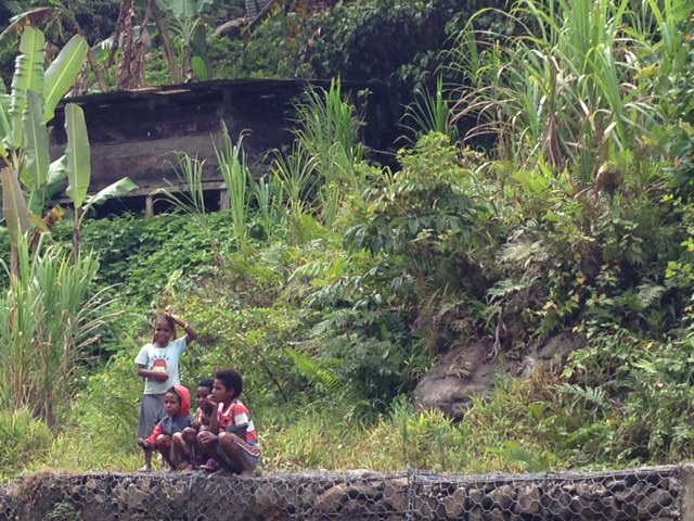 Boys sitting on a rock wall.