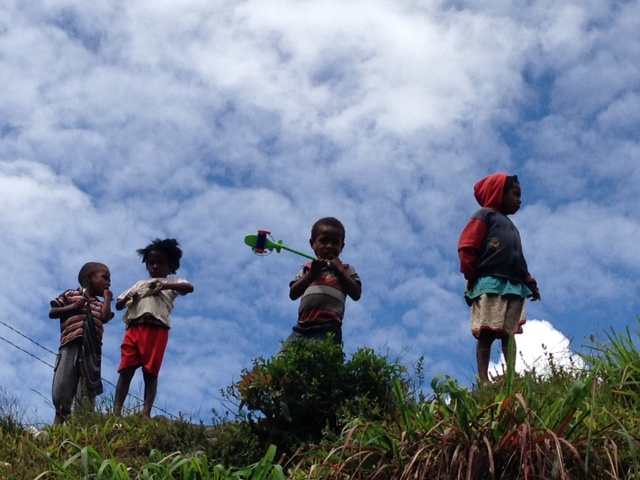 A group of Papuan kids playing with a toy helicopter.