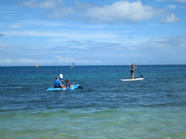 Chris and Kylee riding in a sea kayak, and Ally paddling on a paddle board, in Noumea