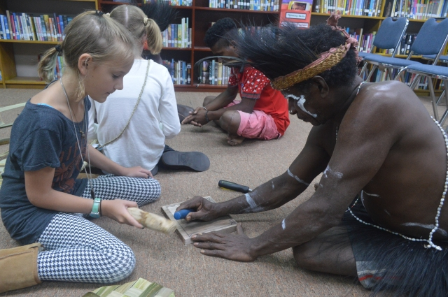 A Komoro tribesman teaching Kylee how to carve wood. Kylee carved a casssowary (a large, mean, flightless bird native to Papua) on her board.