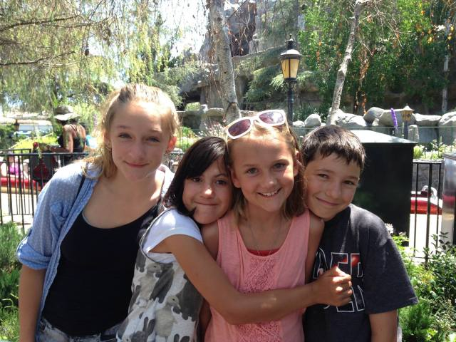 Ally and Kylee, and their cousins Anya and Alex, waiting in line to ride