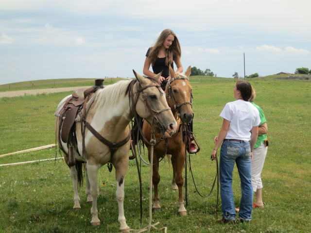 Ally getting on her horse, with the help of kari's daughter,